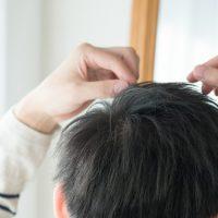 白髪を確認する男性